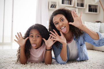 Mother And Daughter Lying On Rug And Pulling Faces At Home