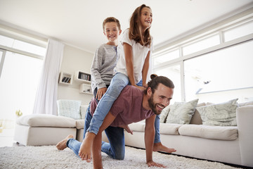 Father Giving Children Ride On Back In Lounge At Home