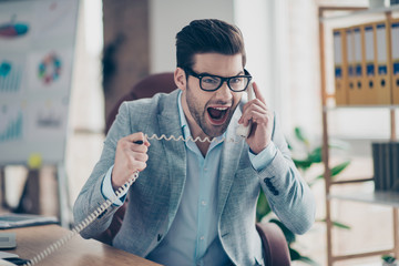 Portrait of aggressive man with modern hairstyle in jacket and shirt is out of himself, shouting at handset, having nervous expression negative emotions sitting in work place