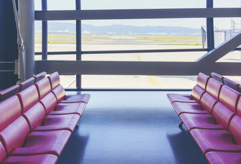 Empty red seats at the gate of international airport terminal viewing beautiful scenery of city from the glass window
