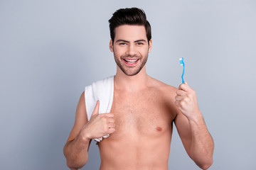 Wellness wellbeing concept. Portrait of neat macho, shirtless muscular model showing teeth brush, having towel on shoulder, isolated on grey background