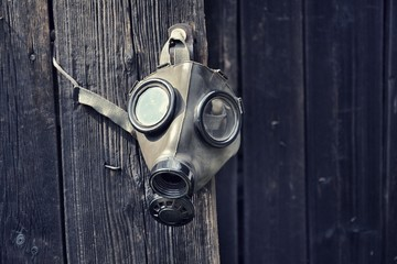 Old gas mask on wooden background, terrorism pollution apocalypse concept