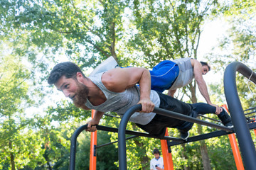 Low-angle view of a strong young man supporting his friend on his back, while doing extreme pull-ups during partner workout in a calisthenics park in summer