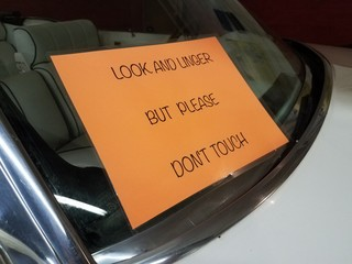 look and linger but please don't touch sign on automobile window