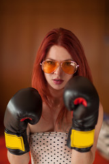 pretty young woman with red hair, sunglasses and boxing gloves looks upset, feminism, self defense concept