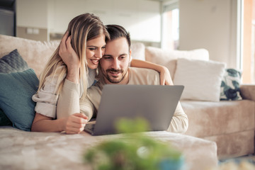 Portrait of cheerful young couple using laptop at home