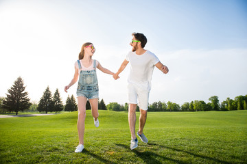 Full length portrait of cheerful positive people in casual outfits sneakers holding hands running on green grass enjoying sun shine having perfect mood. Daydream delight pleasure concept