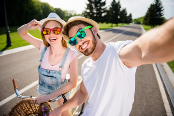 Self portrait of cheerful stylish brother and sister shooting selfie on front camera outdoor while riding on bikes enjoying holidays. Sun adventure photography concept