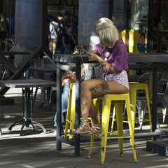 Woman sitting at sidewalk cafe using a mobile phone, Belgrade, Serbia