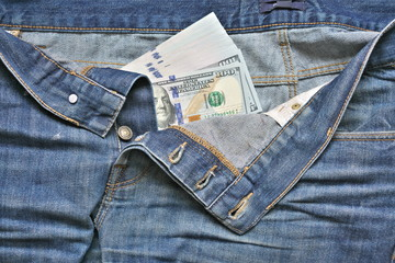 100 American dollars bill sticking out of the blue jeans pocket.