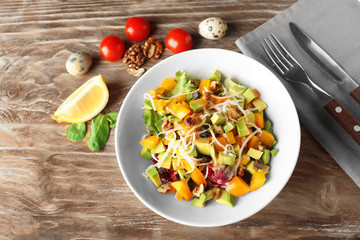 Plate of tasty salad with ripe avocado on wooden table