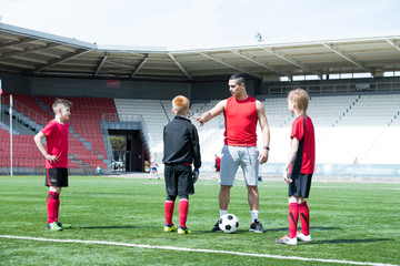 Full length portrait of Latin-American football coach teaching junior team boys in sunlit outdoor  stadium, copy space