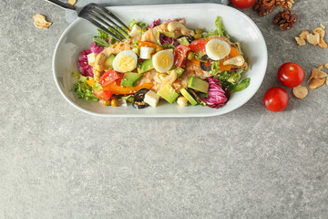 Plate of tasty salad with ripe avocado on table