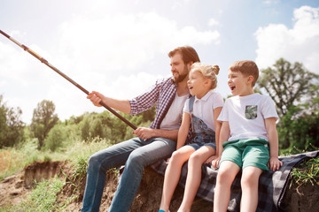 A picture of man and his children sitting together on the river shore. Guy is fishing while his kids are watching on it. Man is holding long fish-rod.