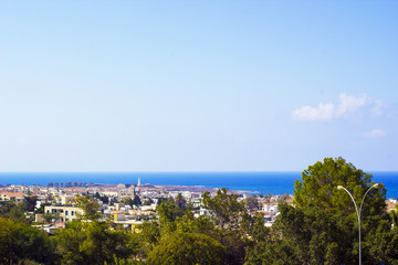 Landscape of town Paphos with houses, trees and sea in distance against blue sky