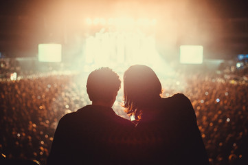 Silhouette of two friends on a rock concert