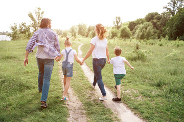 Happy family is walking down the road in meadow. Parents are holding their kids by hands. They are jumping and enjoying the moment.