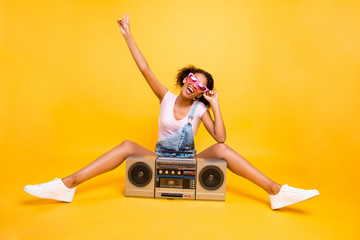 Portrait of fancy crazy girl in eyewear sneakers gesturing v-sign having boom box with cassette tape enjoying stereo sound. Party time music lover fan concept