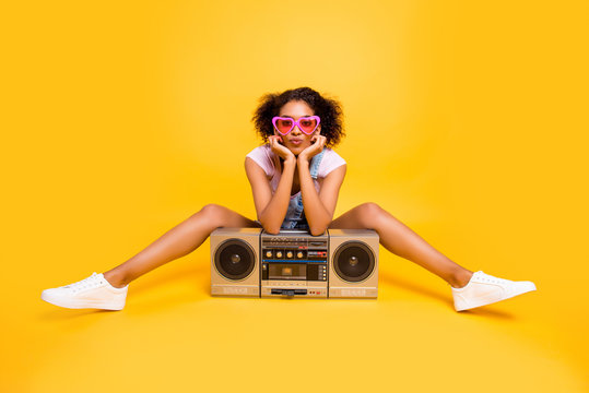 Portrait of sexy charming girlfriend in eyewear having boom box sending kiss with pout lips at camera isolated on yellow background. Leisure rest relax concept