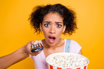 WTF! Head shot portrait of sad upset girl using remote controller having bucket with pop corn missed favorite program lose channel having problem with television