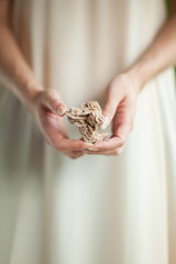 Woman hand holding little crystal mineral rock, sensual studio shot with soft light, can be used as background