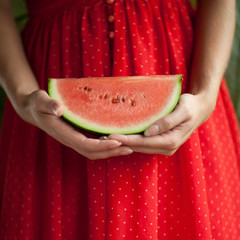 Beautiful woman hands holding a watermelon in her hands, red on red dress, sensual studio shot can be used as background