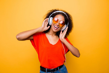 Portrait of cheerful positive woman having headphones on head listening favorite club music singing song dancing isolated on yellow background