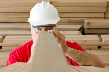 Worker inspecting quality of wooden plank