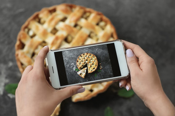 Woman taking photo of tasty homemade apple pie, closeup