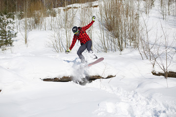 Photo of sportive man riding snowboard in winter park