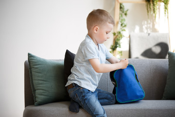 Photo of boy with backpack near sofa
