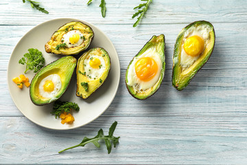 Baked avocados with eggs on wooden table
