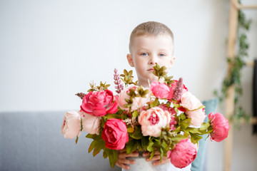 Photo of boy with bouquet of pink peonies