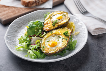Baked avocado with eggs and vegetables on table