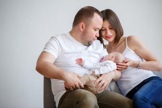 Portrait of happy married couple with newborn baby sitting on sofa