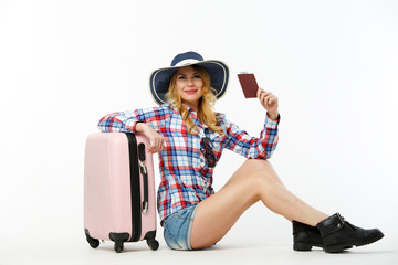 Picture of woman in hat with passport sitting near suitcase