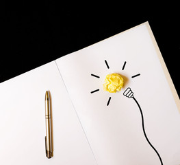 paper bulb on notebook. idea and electricity concept