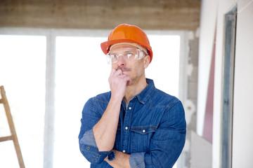 Thinking repairman portrait. Smiling mature construction man portrait with handyman belt and safety helmet