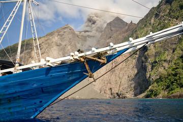 Old boat and active volcano Batu Tara, Indonesia.