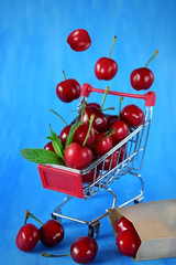 Cherries falling into the shopping cart and scattered around against the blue background