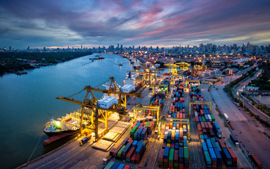 Aerial view of international port with Crane loading containers in import export business logistics with cityscape of Bangkok city Thailand at night Wall mural