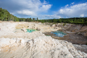 Open pit quarry ore white kaoline mining with blue sky and water