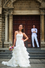 Wedding photo with the bride and groom. Beautiful bride posing against the background of the groom and the Catholic Church