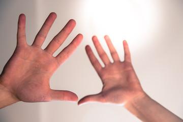 Hände, Schärfe/Unschärfe, Sonnenlicht. Symbolbild für Spiritualität, Therapie oder Sinne.