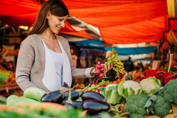 Side view of young woman at farmers market, choosing vegetables.