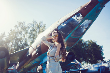 model with long hair in sunglasses against the background of an airplane