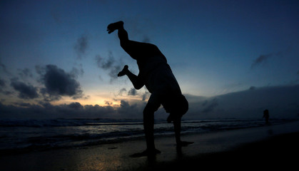 A man performs a physical exercise on a beach in Colombo