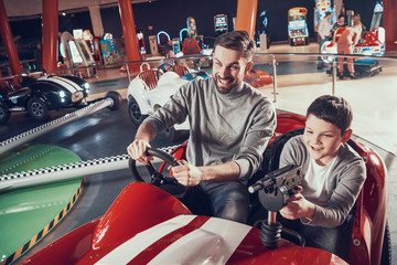 Smiling father and son in amusement center
