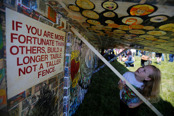 A young girl looks over the Revolving Museum's 64-plus foot long paper airplane in Fitchburg