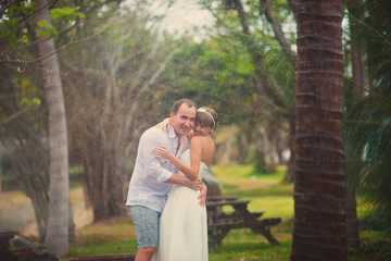 Wedding couple hugging in a tropical Park